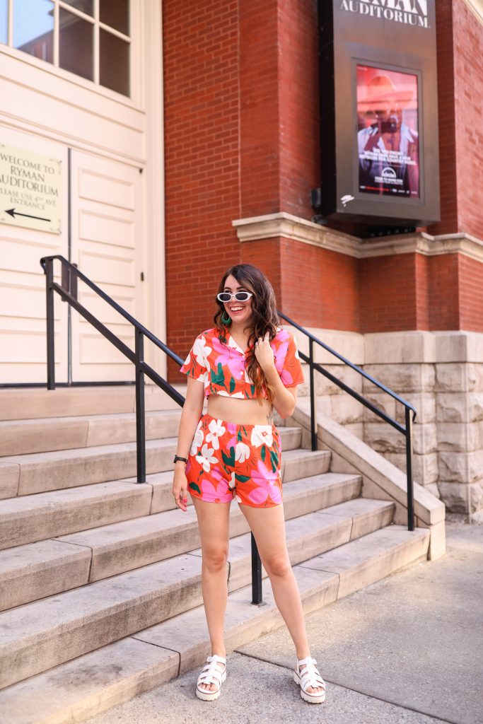 4 Outfit Ideas for Bonnaroo | Greta Hollar | Bonnaroo Outfits by popular Nashville tall fashion blogger, Greta Hollar: image of Greta Hollar wearing a floral crop top and shorts set with white platform sandals, and white frame sunglasses.