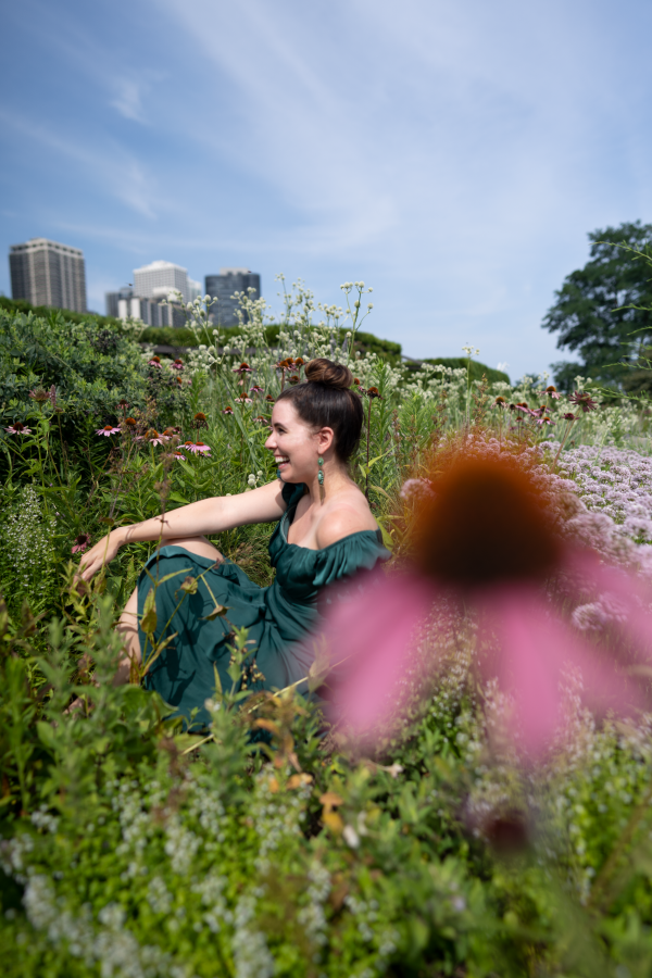 Girls Trip to Chicago: a Complete Weekend Guide | Greta Hollar | Girls Trip to Chicago: a Complete Weekend Guide | Greta Hollar | Girls Trip to Chicago by popular Nashville travel blogger, Greta Hollar: image of Greta Hollar wearing a green off the shoulder dress in sitting in a flower bed.