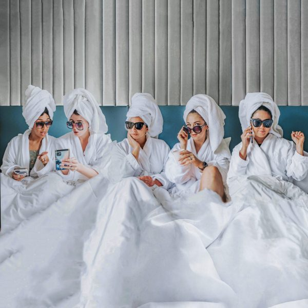 Girls Trip to Chicago: a Complete Weekend Guide | Greta Hollar | Girls Trip to Chicago by popular Nashville travel blogger, Greta Hollar: image of a group of girls wearing white robes, sunglasses, and towels wrapped around their heads while sitting in bed under a white comforter.