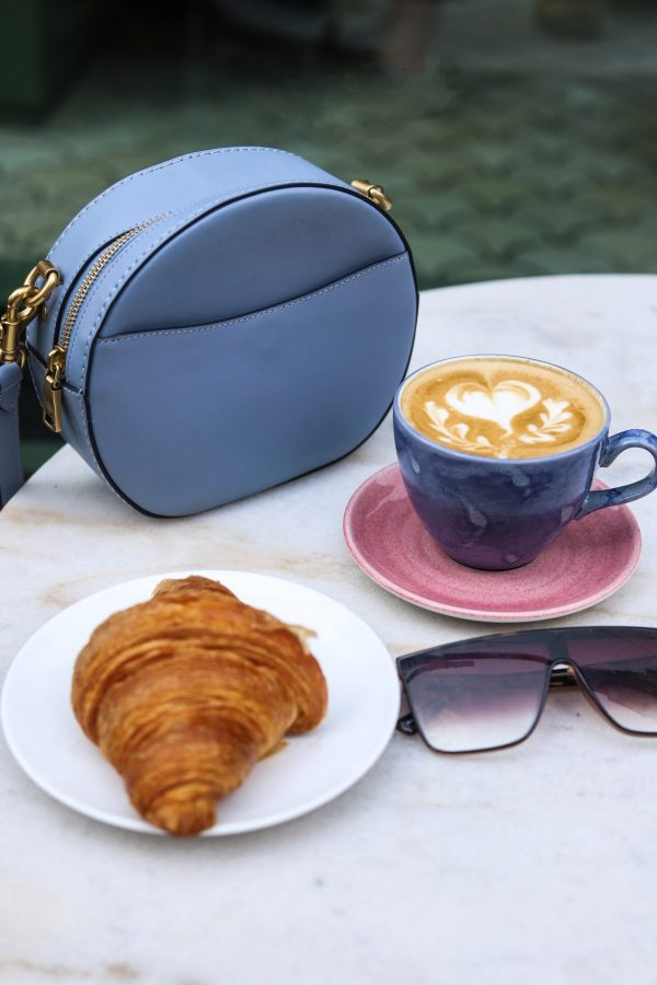 Girls Trip to Chicago: a Complete Weekend Guide | Greta Hollar | Girls Trip to Chicago: a Complete Weekend Guide | Greta Hollar | Girls Trip to Chicago by popular Nashville travel blogger, Greta Hollar: image of a blue circle bag on a table next to a croissant on a white plate, a pair of sunglasses, and a cappuccino.