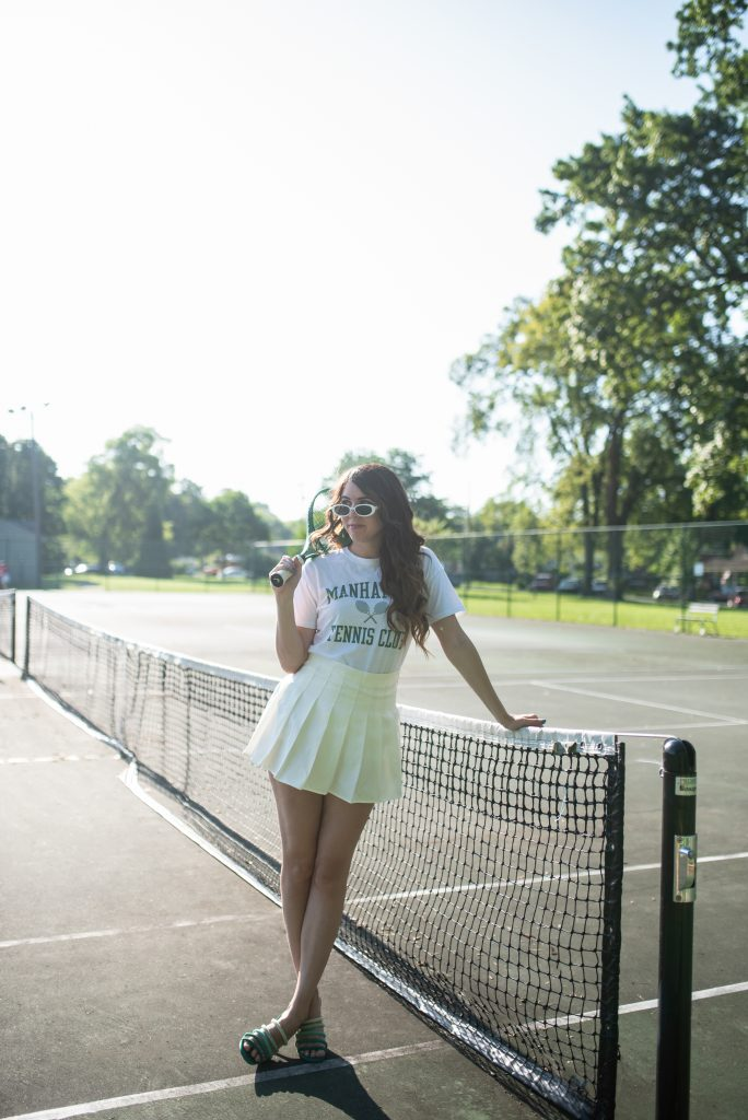 Tennis Outfit by popular Nashville tall fashion blogger, Greta Hollar: image of Greta Hollar holding a green tennis racket and wearing white frame sunglasses, Manhattan graphic t-shirt, and light yellow pleated tennis skirt.