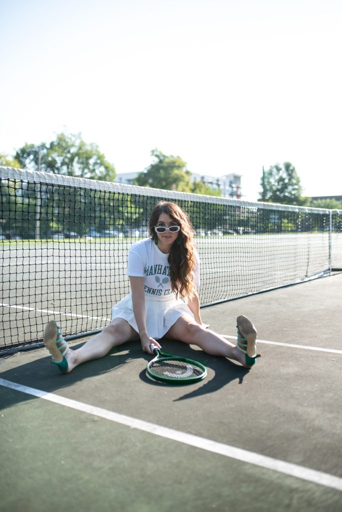 High-Fashion Tennis Outfit | Greta Hollar | Tennis Outfit by popular Nashville tall fashion blogger, Greta Hollar: image of Greta Hollar holding a green tennis racket and wearing white frame sunglasses, Manhattan graphic t-shirt, and light yellow pleated tennis skirt.